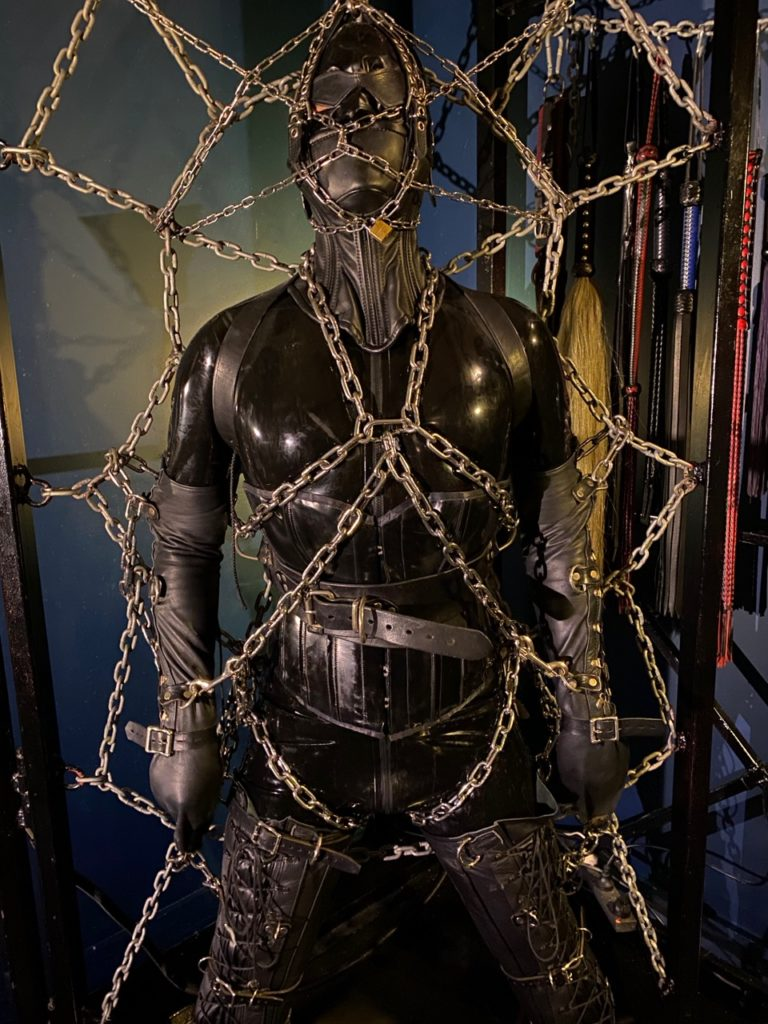 Encased in a latex catsuit and hood Mistress Servalan's slave is restrained to the chain web with leather and metal restraints.